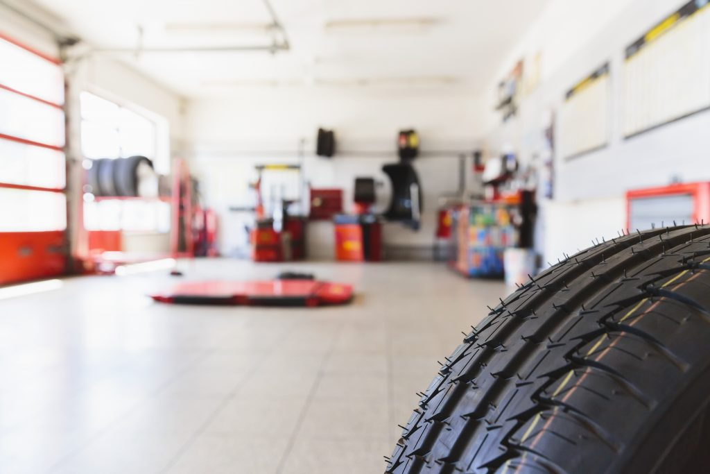 Defocused view into the auto repair shop with a tire in front